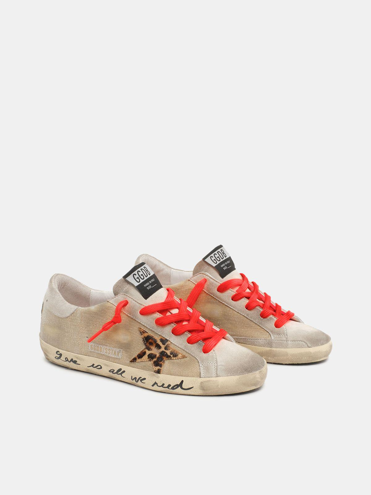 Golden Super-Star sneakers with checkered pattern and hand lettering on the foxing 2