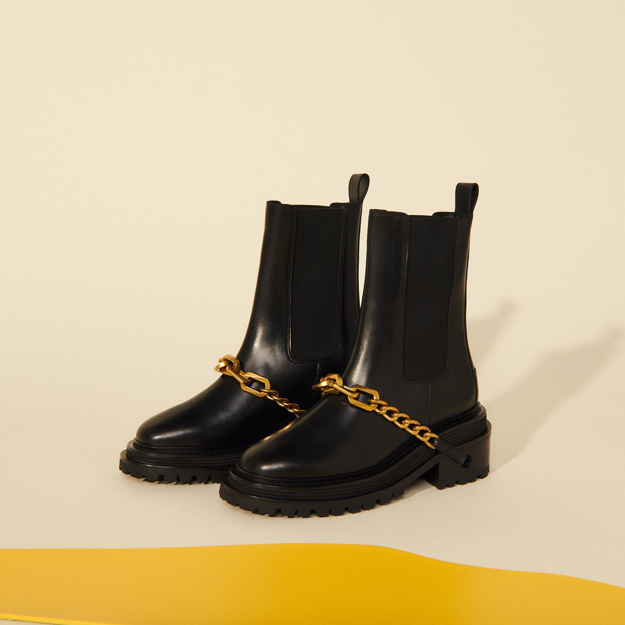 Ankle boots with notched sole and chain