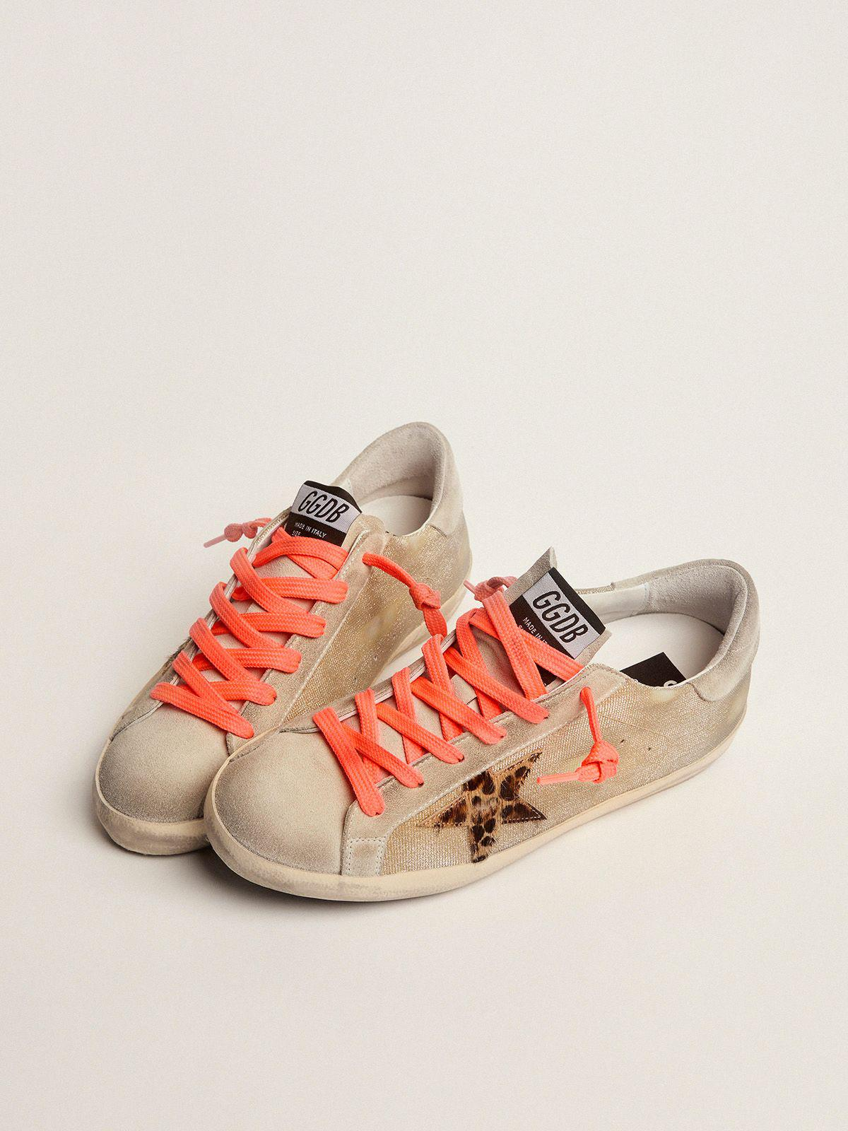 Golden Super-Star sneakers with checkered pattern and hand lettering on the foxing 1